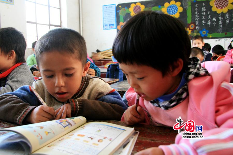 Un garçon ouïgour et une fillette han partagent le même livre.