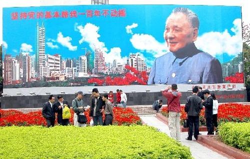 Le 11 avril 2004, des touristes prennent des photos souvenirs devant le portrait de Deng Xiaoping à Shenzhen. Haut de dix mètres et large de 30, ce portrait a été réalisé le 28 juin 1992. Plus d'un million de touristes posent avec le grand homme chaque année.