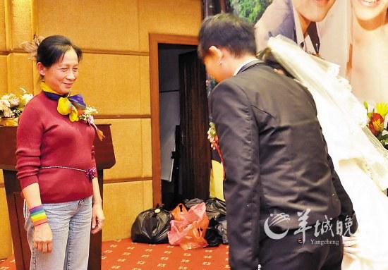 Mme Wu Youjian, la première mère qui soutient publiquement l'homosexualité de son fils dans la partie continentale de Chine, accepte le salut des nouvelles mariées.