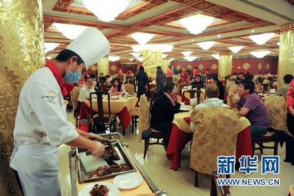 Le 30 janvier, un cuisinier du restaurant Quanjude de Beijing découpe un canard laqué en tranches.