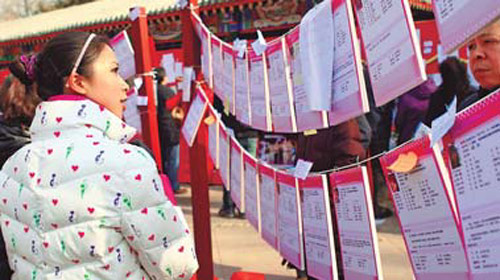 Une femme scrute une petite annonce sur une pancarte du parc Ditan de Beijing.