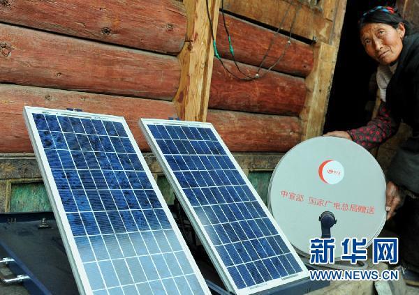Le 23 avril, Zhanma, une paysanne du village de Dumuling, ajuste l'antenne de réception satellite du téléviseur digital.
