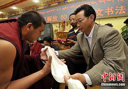Un membre du jury offre une hada à un moine lauréat.