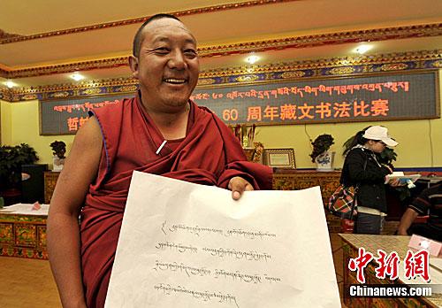 Un moine lauréat présente son œuvre calligraphique.