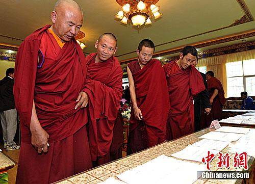 Les membres du jury et les moines admirent les œuvres calligraphiques.