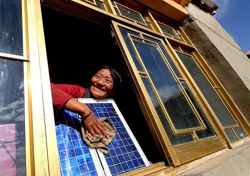 Une femme tibétaine nettoie un panneau solaire dans sa nouvelle maison, dans le district de Nierong. Photo prise le 12 octobre 2006.