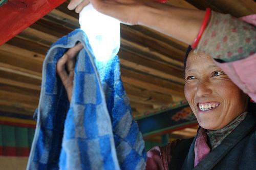 Une femme tibétaine installe une lampe solaire sur sa nouvelle maison.