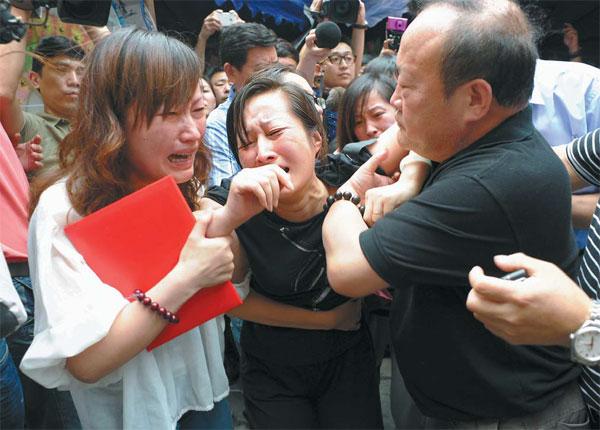 Wang Lizhen (au centre), l'épouse du chauffeur d'autobus Wu Bin, et des parents sont accablés de chagrin, dimanche. Le courage de M. Wu a frappé l'imagination du public.