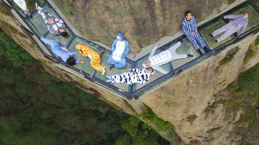 Hunan : des touristes se couchent sur une passerelle en verre au-dessus d'une falaise