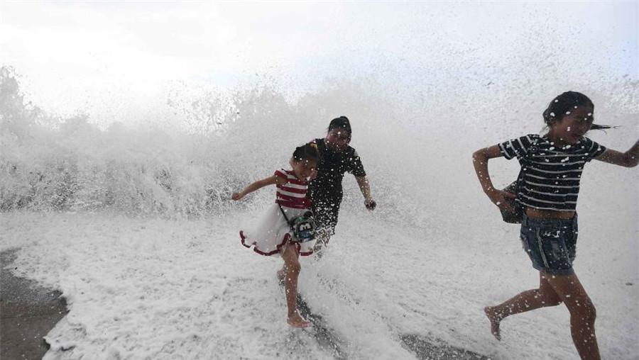 Qingdao : des touristes s'amusent avec de grands mascarets