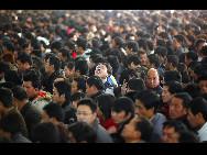 Auf dem Shanghaier Bahnhof warten die Passagiere darauf, Fahrkarten zu kaufen.