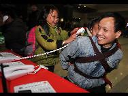 Auf dem Bahnhof von Hangzhou rufen Lu Laofa, ein Wanderarbeiter aus Guizhou, und seine Kinder vor ihrer Rückkehr in die Heimat kostenfrei ihre Familie an. Zum diesjährigen Frühlingsfest werden rund 20 Millionen Wanderarbeiter aus der Provinz Zhejiang heimkehren. Für die Wanderarbeiter bietet der Bahnhof Hangzhou kostenlose Anrufe nach Hause an.