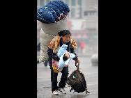 Im Bahnhof von Nanchang, der Hauptstadt der zentralchinesischen Provinz Jiangxi, trägt eine Wanderarbeiterin ein riesiges Bündel und ihr Baby.