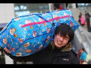 Ein Wanderarbeiter trägt sein Gepäck und geht zum Bahnhof von Yantai, einer Stadt in der ostchinesischen Provinz Shandong.