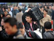 Ein Passagier trägt einen Koffer im Bahnhof von Guangzhou.