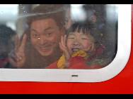 In einem Zug, der gerade aus dem Bahnhof Shenzhen fährt, zeigt sich eine Familie erfreut darüber, dass sie nach Hause fahren kann.