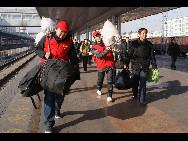 Auf dem Bahnhof von Hohhot, der Hauptstadt der Inneren Mongolei tragen zwei Freiwillige das Gepäck der Passagiere.