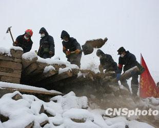 Das Volksmiliz-Rettungsteam beschäftigt sich mit der Rettungsarbeiten im Schnee in Yushu (22. April 2010). Seit Frühmorgen am Donnerstag hat es im Erdbebengebiet Yushu in der westchinesischen Provinz Qinghai geschneit. Die Rettungsarbeiten wurden hierdurch erschwert