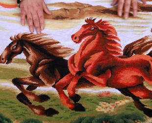 Huo Yuexia zeigt eine 2,5 Meter lange Kreuzstickarbeit zum Thema Pferd 'Madao Chenggong'. Auf Deutsch bedeutet das: Man hat Erfolg, wenn das Kriegspferd ankommt.