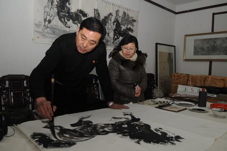 Das Foto zeigt, wie Liu Xufeng (links), Mitglied des Malervereins der Provinz Shandong, am 15. Januar in der Wenfeng-Akademie für Kalligrafie und Malerei, die im Bezirk Zichuan der Stadt Zibo liegt, mit Tusche ein Pferd malt.