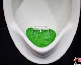 Das Bild zeigt ein Fußball-Urinal in einer Herrentoilette eines Einkaufszentrums in Shanghai. Mit grünen Urinalmatten, die wie ein Fußballplatz aussehen, und fußballförmigen Toiletten-Duftkugeln will das Einkaufszentrum die WM 2014 hochleben lassen.