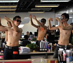 Halbnackte junge Männer führen am 29. Juli 2014 den Tanz 'Kleiner Apfel' für Büro-Damen in einem Büro in Beijing auf, um das bevorstehende Qixi-Festival, den chinesischen Valentinstag, zu feiern.