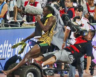 Usain Bolt (l.) aus Jamaika wird von einem Kameramann auf einem Segway umgefahren, nachdem er das Finale im 200m-Sprint der Männer auf der 15. IAAF Leichtathletik-Weltmeisterschaften im Nationalstadion in Beijing am 27. August 2015 gewonnen hat.