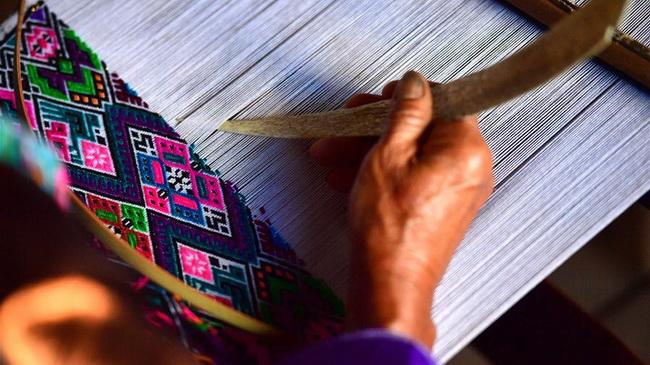Eine Zugehörige der ethnischen Gruppe der Miao, Li Yiyuan (M.) zeigt Kunden Stickereien in ihrem Atelier in Rongshui.