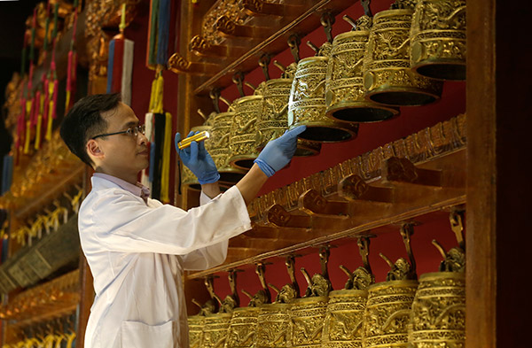 An expert checks the Set of Bronze Bells with Double-Dragon Knob and Dragon-Cloud Design collection of the Palace Museum, dating from the 52nd year of the Kangxi reign (1713), as crates are opened at the Hong Kong Museum of History.Roy Liu / China Daily