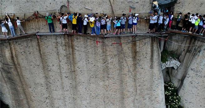 Mutprobe am Hua Shan: Touristen gehen über schmalen Steg an Felswand
