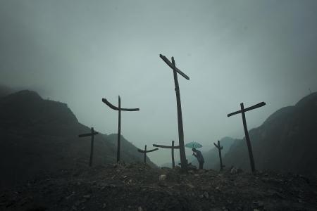 一名参观者站在废墟上向地震死难者低头默哀。