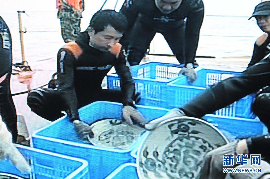 明代沈没船「南澳1号」から発掘された磁器を整理する発掘作業員(動画による写真)