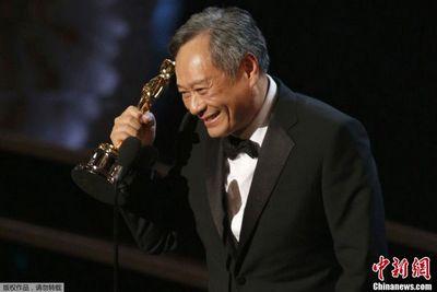 Счастливый режиссер Ли Ань ест гамбургер на улице, держа «Оскара» в руке
