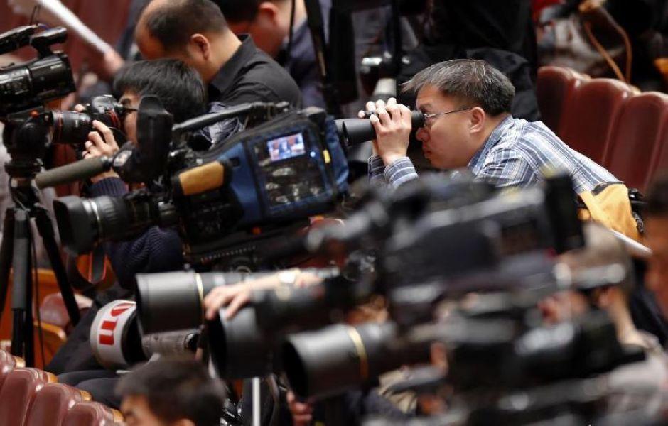 Журналист с биноклем наблюдает за 2-м пленарным заседанием в рамках 2-й сессии ВСНП