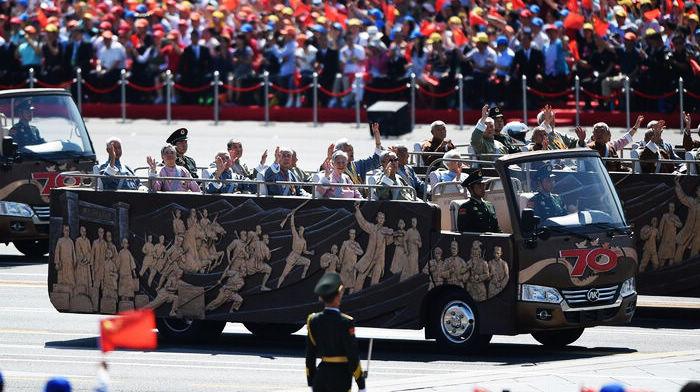 Через площадь Тяньаньмэнь проезжает строй ветеранов войны