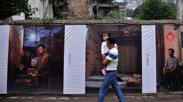 Фотопортреты переселенцев, развешенные на стенах «Восемнадцати лестниц» в Чунцине, привлекли внимание множества посетителей