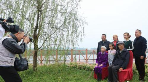 В районе Пэншан провинции Сычуань 99 семей, в которых четыре поколения живут под одной крышей, фотографируются всей семьей в преддверии Праздника Чунъян
