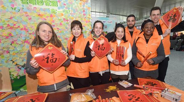 Иностранные волонтеры работают на ханчжоуском железнодорожном вокзале во время новогоднего пика пассажирских перевозок