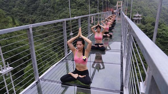 Йога на стеклянном висячем мосту в ландшафтном парке Тайцзися
