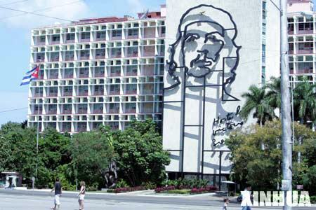 People walk past the building of Cuba's Interior Ministry, which is decorated with a portrait of Che Guevara, in Havana, Cuba, Feb. 23, 2008. Cuba has completed all preparations for the elections of a new president and other national leaders, and the elections will proceed on Sunday as scheduled, President of the National Electoral Commission and Justice Minister Maria Esther Reus said on Saturday. The Cuban National Assembly of People's Power will be convened on Sunday, when the 614 deputies elected last month will be called to create the country's new legislature.(