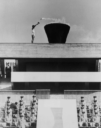 Yoshinori Sakai, who was born in Hiroshima on the day the first atomic bomb devastated the city, lights the Olympic Flame in Tokyo's main stadium during the opening ceremony of the Olympic Games, on October 10, 1964.