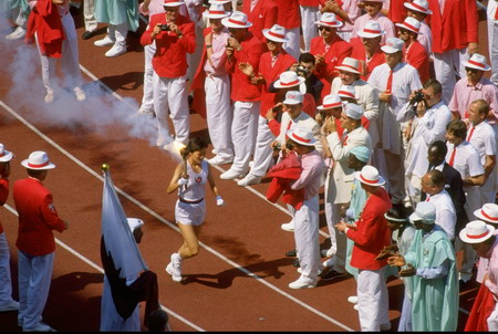 Delegates acknowledge the arrival of the Olympic Flame in the Olympic Stadium during the opening ceremony of the 1988 Olympic Games in Seoul, South Korea.