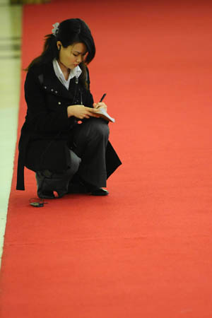 A journalist squats to take notes during Chinese Foreign Minister Yang Jiechi's meeting with the press at the Great Hall of the People in Beijing, capital of China, March 12, 2008. 