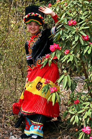A girl of the Yi ethnic group walks through the flowers in the Guizhou Baili Azalea National Forest Park in Qianxi County, southwest China's Guizhou Province, March 28, 2008. An azalea festival scheduled to last one month opened here on Friday.