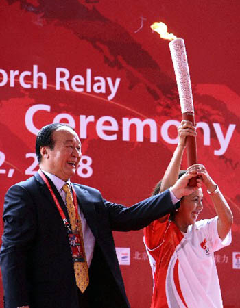 Jiang Xiaoyu (L), vice president of the Beijing Organizing Committee of Olympic Games (BOCOG), handed over the torch, which was kindled with the sacred Olympic flame from ancient Olympia of Greece, to Rita Subowo, president of the National Olympic Committee of Indonesia.