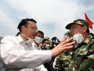 Chinese Vice Premier Li Keqiang (L), also member of the Standing Committee of the Political Bureau of the Communist Party of China (CPC) Central Committee, speaks to a rescuer during his visit to the quake-hit southwest China's Sichuan Province to direct quake relief on May 19, 2008. (Xinhua Photo)