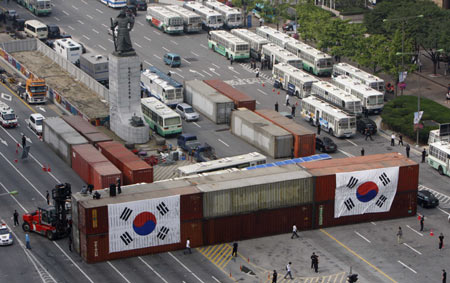 Police place South Korean flags on cargo containers that hold sand to form a barricade to block a planned protest march on a street leading to the U.S. embassy and the presidential Blue House in central Seoul June 10, 2008. The containers were welded together and on to the road. About one million people fearing infection of mad cow disease across the country will demonstrate Tuesday evening to demand full-scale renegotiation of a beef deal with the U.S. and the resignation of President Lee Myung-bak as they commemorate the historic June 10 mass pro-democracy demonstrations in 1987.
