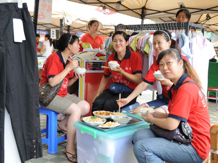 Sales girls eat their lunch in a tent market in the quake-hit Jiangyou city, southwest China's Sichuan Province, on June 13, 2008. Local government has set up about 2,455 tent stores in the quake-hit areas and more than 200 board-house markets at the makeshift shelters to ensure the quake victims' daily need. (Xinhua Photo)