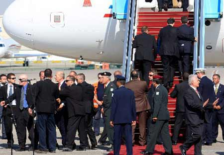 France's President Nicolas Sarkozy (center R) is rushed by security officers into the presidential plane at Ben Gurion international airport near Tel Aviv June 24, 2008.