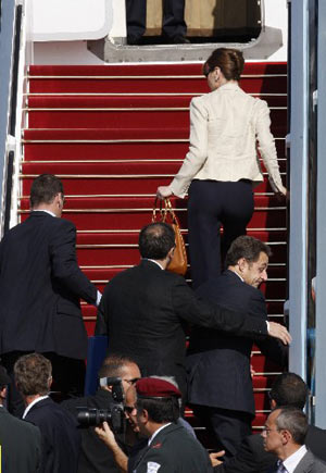 France's President Nicolas Sarkozy (center R) and his wife Carla Bruni-Sarkozy (top) are rushed by security officers into the presidential plane at Ben Gurion international airport near Tel Aviv June 24, 2008.